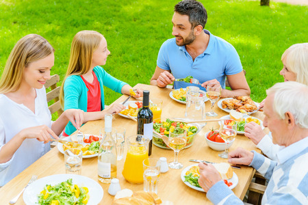 lifestyle dining: Enjoying dinner together. Top view of happy family of five people communicating and enjoying meal together while sitting at the dining table outdoors Stock Photo