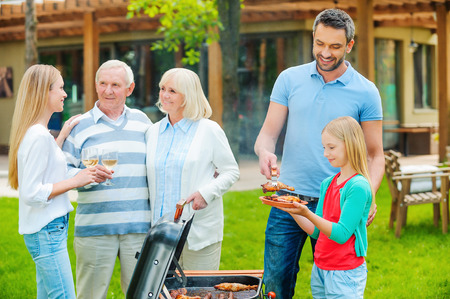 barbecuing: Spending great time with family. Happy family of five people barbecuing meat on grill on the back yard