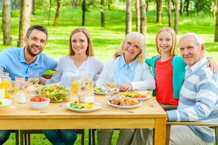 a little dinner: Family together. Happy family of five people bonding to each other and smiling while sitting at the dining table outdoors