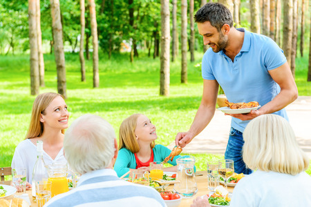 social gathering: Enjoying time with family. Happy family of five people enjoying meal together while sitting at the dining table in formal garden