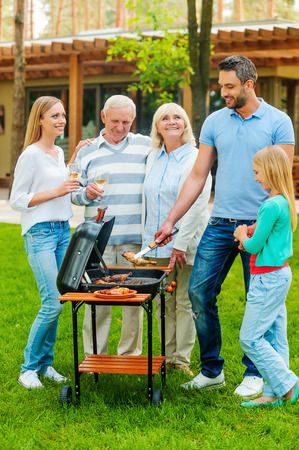 family garden: Time for barbeque. Full length of happy family barbecuing meat on grill outdoors