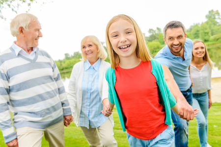 Having fun with family. Happy little girl enjoying time with her family while walking outdoors together photo