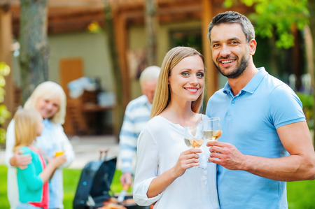 Enjoying summer barbeque with family. Happy young couple bonding to each other and holding wine glasses while other members of family barbecuing food in the background photo