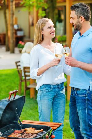 tomando vino: Disfrutar de la barbacoa de verano. Feliz pareja de jóvenes barbacoa carne en el asador y bebiendo vino, mientras que otros miembros de la familia que se sienta en la mesa de comedor en el fondo