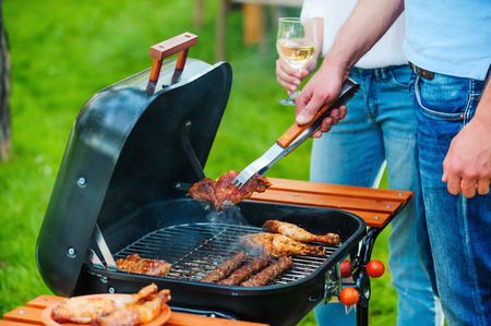 Close-up of two people barbecuing meat on the grill while standing outdoors Stock Photo
