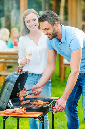 barbecuing: Need some help? Happy young couple barbecuing meat on the grill while other members of family sitting at the dining table in the background Stock Photo