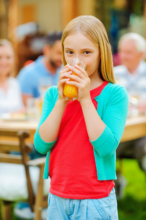 Enjoying fresh juice. Cute little girl drinking orange juice and smiling while her family sitting at the dining table in the background photo