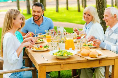 personas comunicandose: Tiempo familiar. Familia feliz de cinco personas que se comunican y disfrutando de comida juntos mientras estaba sentado en la mesa de comedor al aire libre Foto de archivo