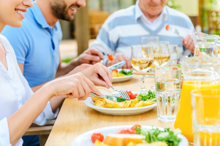 comidas: Cena familiar. Primer plano de la familia comida disfrutando juntos mientras se está sentado en la mesa de comedor al aire libre