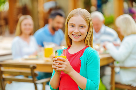 dining out: Enjoying time with family. Happy little girl holding glass with orange juice and smiling while her family sitting at the dining table in the background Stock Photo