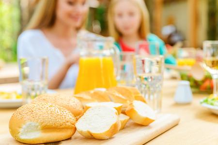 comiendo pan: El pan más fresco para la cena. Madre feliz con su hija sentada en la mesa de comedor al aire libre y disfrutar de la comida mientras que el pan fresco que pone en primer plano Foto de archivo