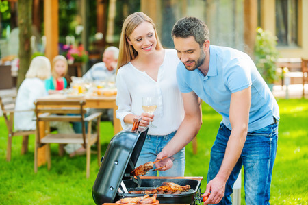 family meal: Family barbeque. Happy young couple barbecuing meat on the grill while other members of family sitting at the dining table in the background