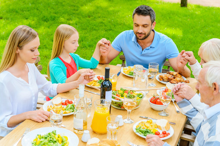 holding hands: Praying before dinner. Top view of family of five people holding hands and praying before dinner while sitting at the table outdoors Stock Photo