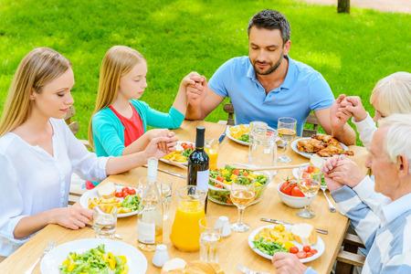familia orando: Rezar antes de la cena. Vista superior de la familia de cinco personas de la mano y orando antes de la cena mientras se está sentado en la mesa al aire libre
