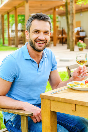 outdoor pursuit: Enjoying dinner outdoors. Happy young man holding glass with wine and smiling while sitting at the dining table outdoors