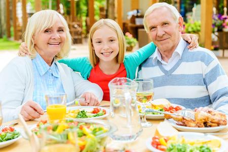 mixed age range: Tiempo con los abuelos Disfrutar. Ni�a feliz abrazando a sus abuelos y mirando a la c�mara mientras est� sentado en la mesa de comedor al aire libre junto