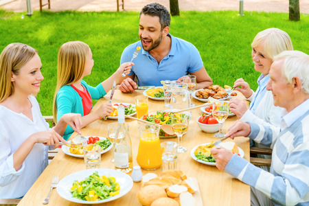 Family dining together. Top view of happy family of five people communicating and enjoying meal together while sitting at the dining table outdoors