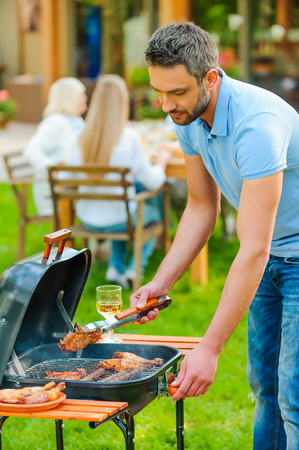 mixed age range: Barbecuing meat to perfection. Confident young man barbecuing meat on the grill while other members of family sitting at the dining table in the background
