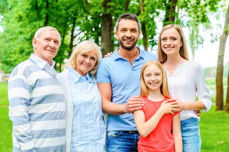 familie: Gelukkig om een gezin te zijn. Gelukkig gezin van vijf mensen verlijmen met elkaar en glimlachen terwijl elkaar staande buiten