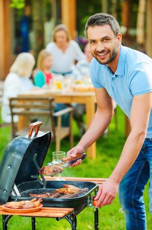 parrillero: Disfrutar de barbacoa familiar. Hombre joven feliz barbacoa de carne a la parrilla y sonriendo mientras otros miembros de la familia que se sienta en la mesa de comedor en el fondo