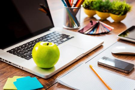 apfel: Snack für die Produktivität des Unternehmens. Close-up ofcomfortable Arbeitsplatz im Büro mit Holztisch und Laptop mit auf