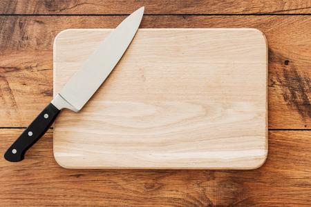 Close-up bovenaanzicht van houten snijplank en mes leggen op