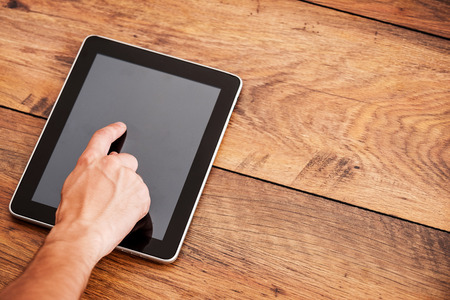 Close-up of man touching digital tablet laying on wooden desk Stok Fotoğraf