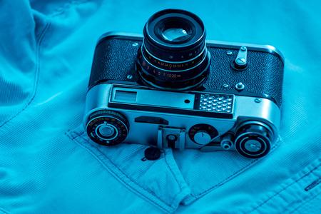 retro styled: Retro styled camera. Close-up of retro camera laying on blue shirt Stock Photo