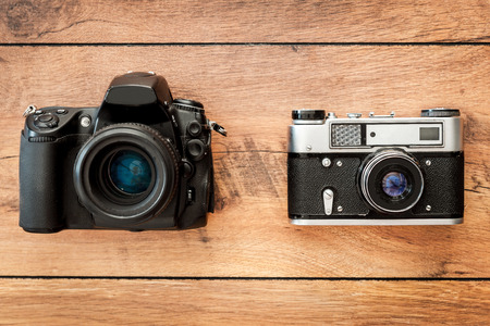 photography themes: Modern or retro? Top view of two cameras laying on the wooden grain