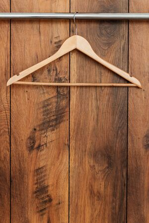 coathanger: Wooden coat hanger. Close-up of hanger hanging against wooden grain Stock Photo
