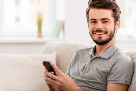 mp3 player: Enjoying his favorite music. Cheerful young man in headphones holding MP3 player and looking at camera while sitting on sofa Stock Photo