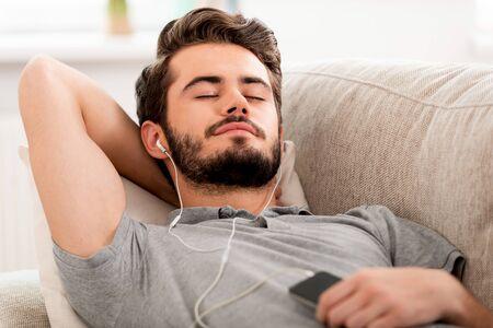 escuchando musica: Hombre barbudo sonriente en los auriculares con la mano detrás de la cabeza y manteniendo los ojos cerrados, mientras que pone en el sofá