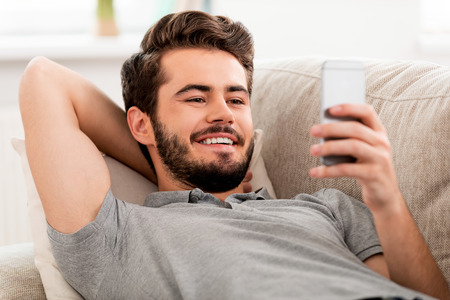 resting: Smiling bearded man holding mobile phone and looking on it while laying on sofa