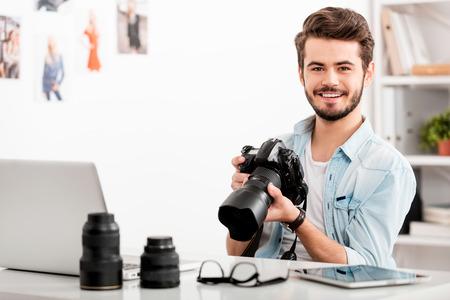 陽気な若い男がデジタル カメラを持って、彼の職場に座って笑顔