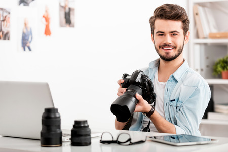 Cheerful young man holding digital camera and smiling while sitting at his working place Banco de Imagens