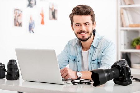 office workers: Smiling young man working on laptop and looking at camera while sitting at his working place Stock Photo