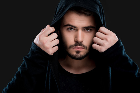 hood: Serious young man adjusting his black hood and looking at camera while standing against black background