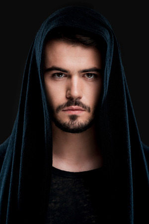 hood: Confident young man in black hood looking at camera while standing against black background Stock Photo