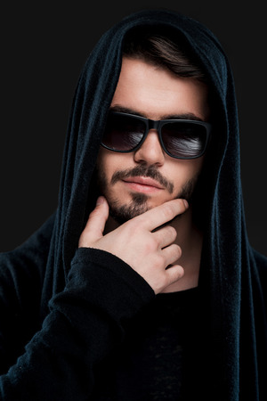 male models: Confident young man in black hood holding hand on chin and looking at camera while standing against black background