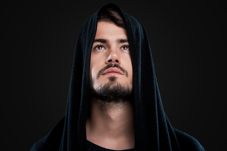 man looking: Handsome young man in black hood looking up while standing against black background Stock Photo
