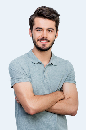 Candid smile. Handsome young man keeping arms crossed and looking at camera while standing against white background Foto de archivo