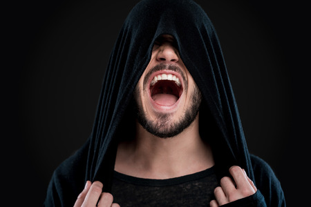 unleashed: Unleashed emotions. Young man covering his face by black hood and shouting while standing against black background