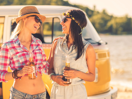near beer: Best friends ever. Two cheerful young women holding bottles of beer and looking at each other with smiles while standing near retro mini van Stock Photo
