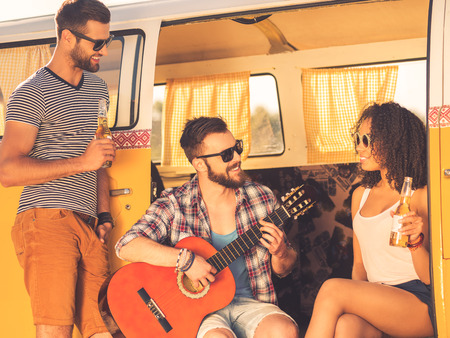 minivan: Enjoying great time together. Cheerful young beard man sitting in retro minivan and playing guitar while two his friends looking at him and smiling