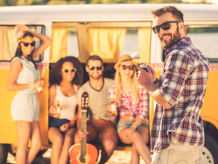 retro styled: Capturing bright moments. Smiling young man holding retro styled camera and looking over shoulder while four young cheerful people sitting in retro minivan in the background