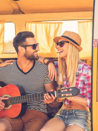 pareja enamorada: Pasar tiempo juntos sin preocupaciones. Apuesto joven sentado en la camioneta y tocando la guitarra mientras que su novia unir a él y sonriente