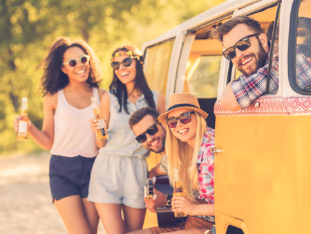 brighter: Life is brighter when friends are near. Group of cheerful young people enjoying time together while sitting and standing near their retro minivan Stock Photo