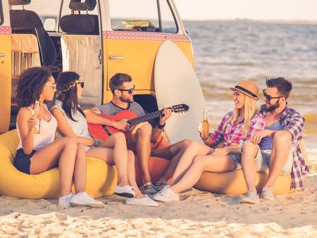 hombre tomando cerveza: Diversi�n de verano. Grupo de j�venes alegres que beben cerveza y tocando la guitarra mientras est� sentado en la playa cerca de su minivan retro Foto de archivo