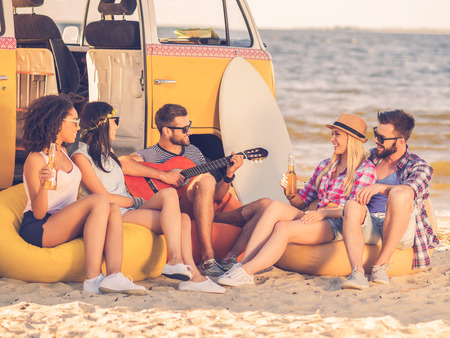 summer: Summer fun. Group of joyful young people drinking beer and playing guitar while sitting on the beach near their retro minivan