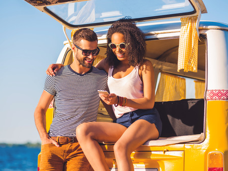 minivan: Look at this photo! Cheerful young couple looking at mobile phone together while both sitting at the trunk of retro minivan with sea in the background Stock Photo